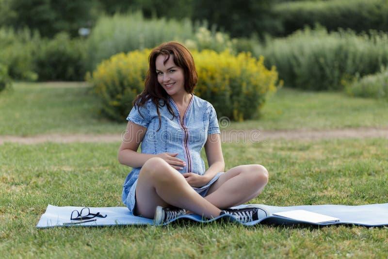 Mulher gravida nova que trabalha no parque usando seu portátil imagens de stock