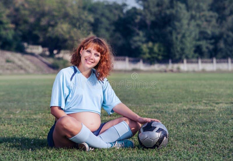 Mulher gravida nova vestida no uniforme do futebol imagem de stock