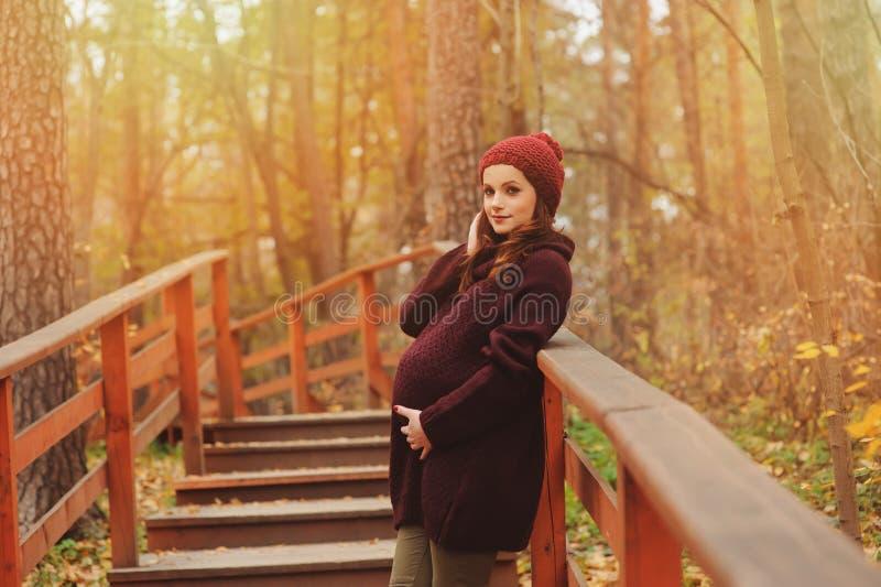 Mulher gravida pensativa no equipamento acolhedor brandamente morno do marsala que anda fora imagens de stock