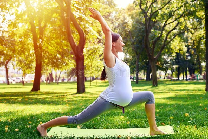 Mulher gravida positiva que medita na pose da ioga fora imagem de stock
