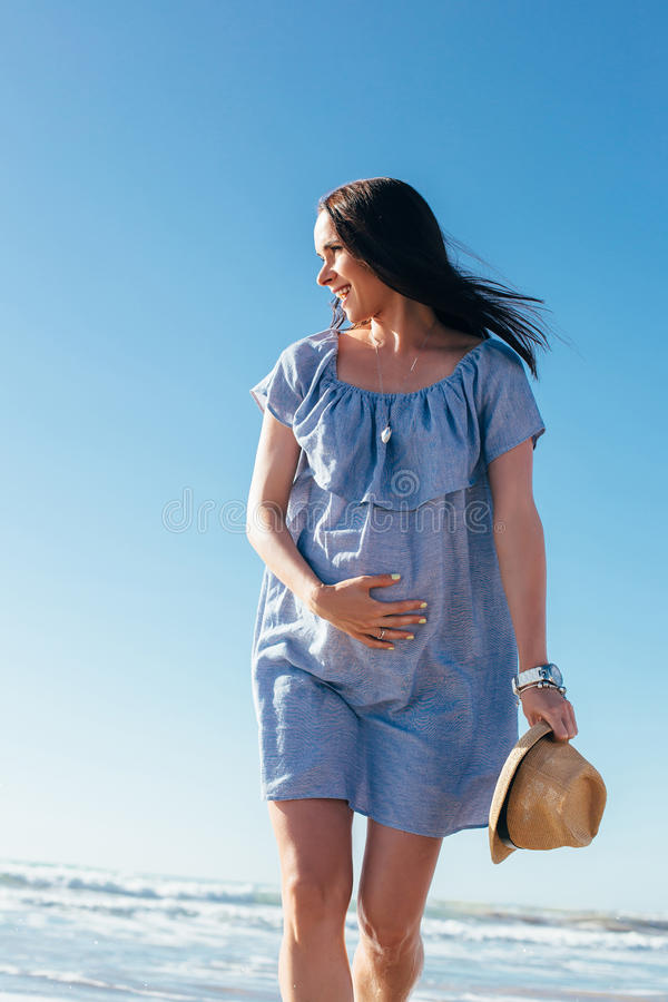 Mulher gravida que anda na praia imagens de stock