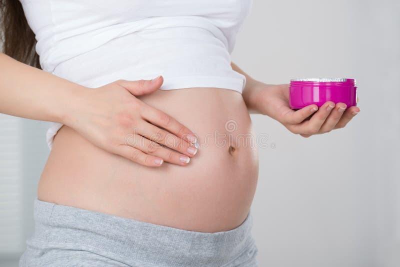 Mulher gravida que aplica o creme em sua barriga fotos de stock royalty free