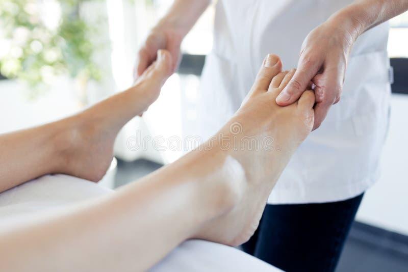 Mulher gravida que aprecia a massagem do pé do reflexology em termas do bem-estar fotos de stock