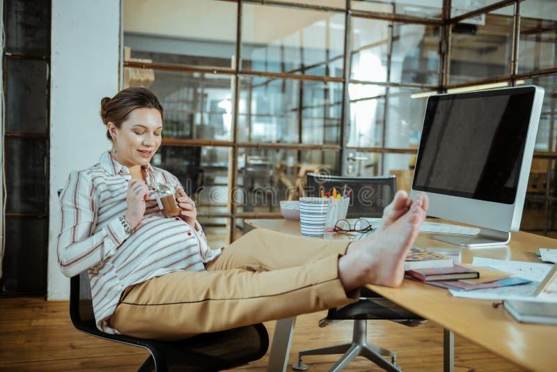 Mulher gravida que coloca os pés na tabela que come a musse de chocolate fotos de stock royalty free
