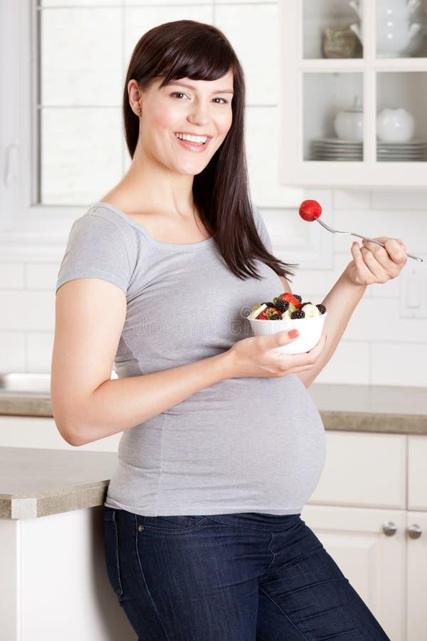 Mulher gravida que come o petisco saudável fotografia de stock royalty free