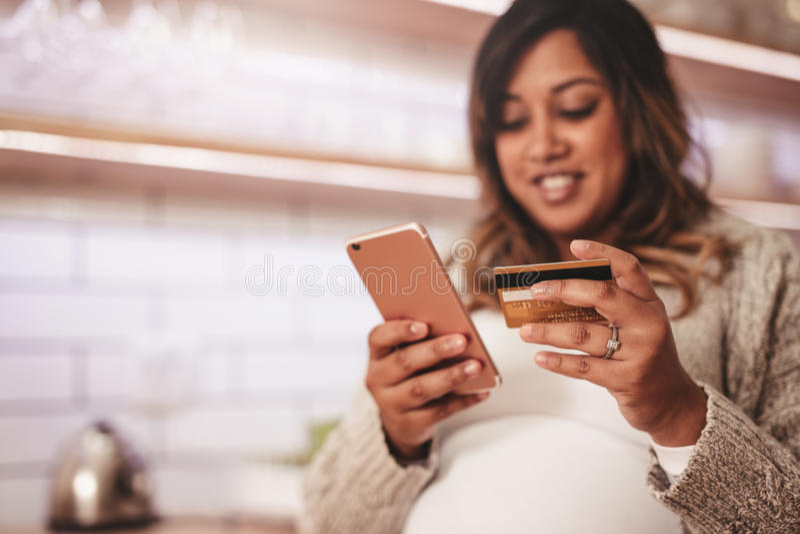 Mulher gravida que compra em linha com cartão e telefone celular de crédito foto de stock