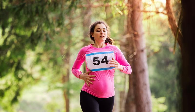 Mulher gravida que corre uma competição da raça na natureza fotos de stock royalty free
