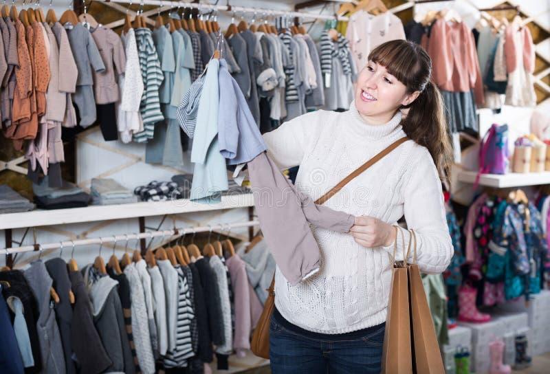 A mulher gravida que decide na roupa para o bebê nos children's coagula fotos de stock
