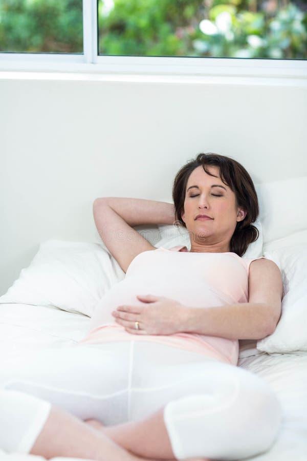 Mulher gravida que descansa em sua cama fotos de stock royalty free