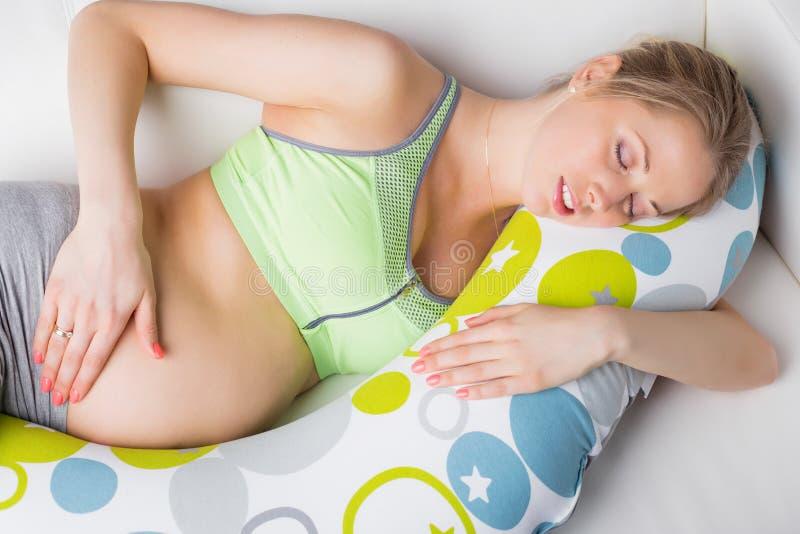 Mulher gravida que dorme no descanso imagens de stock