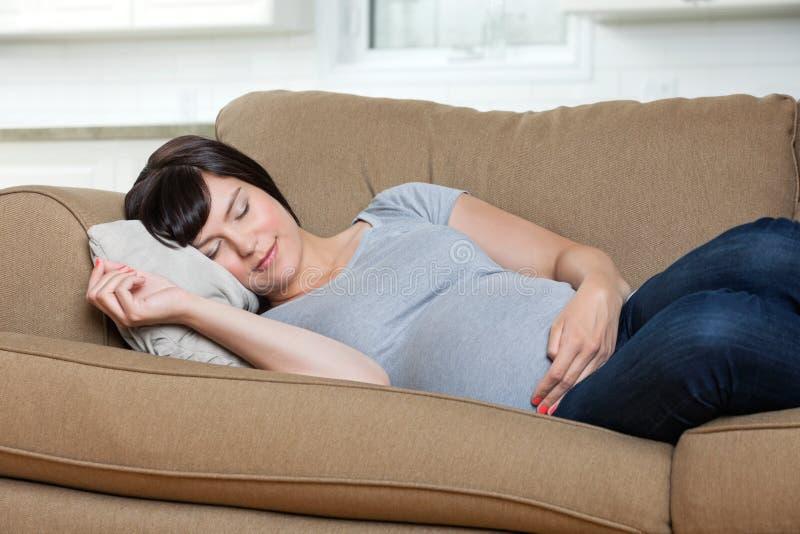 Mulher gravida que dorme no sofá fotografia de stock royalty free