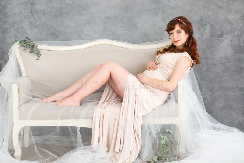 Mulher gravida que encontra-se em um sofá em um vestido bege bonito, embreando seu estômago com suas mãos imagens de stock royalty free