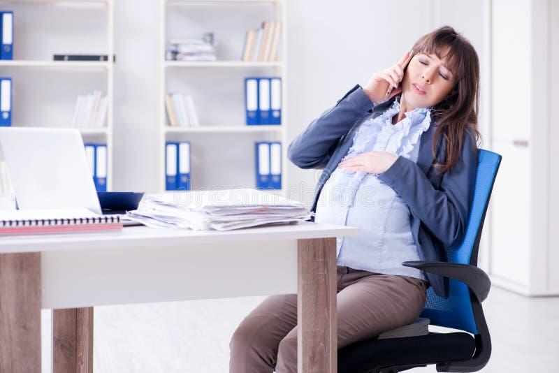 A mulher gravida que esforça-se para fazer o trabalho no escritório fotografia de stock