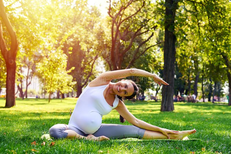 Mulher gravida que estica na esteira da ioga no parque foto de stock