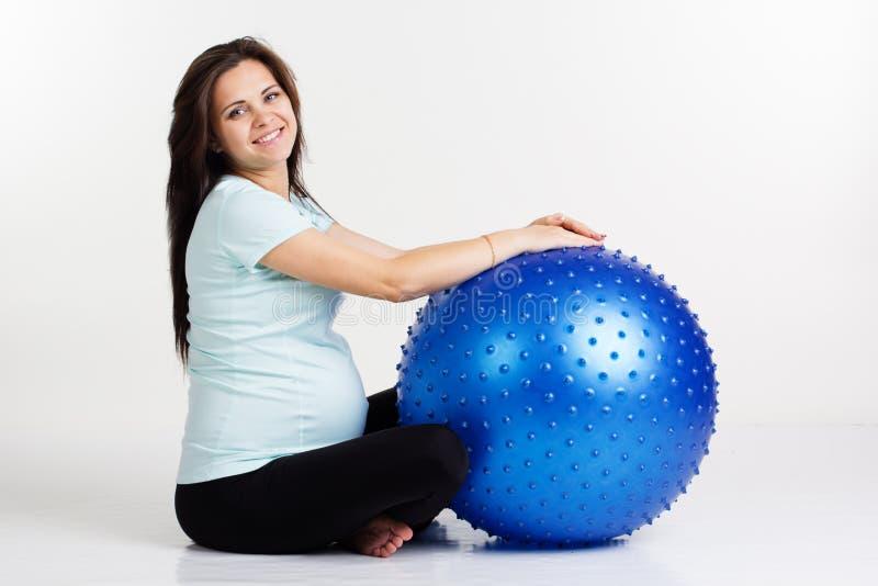 Mulher gravida que exercita a aptidão com bola azul fotografia de stock