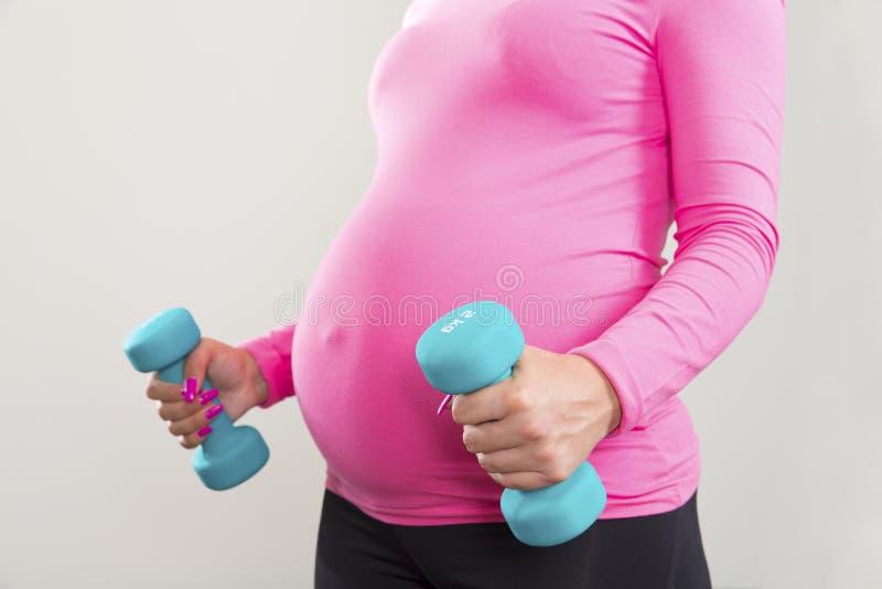 Mulher gravida que exercita com os pesos de formação internos fotografia de stock