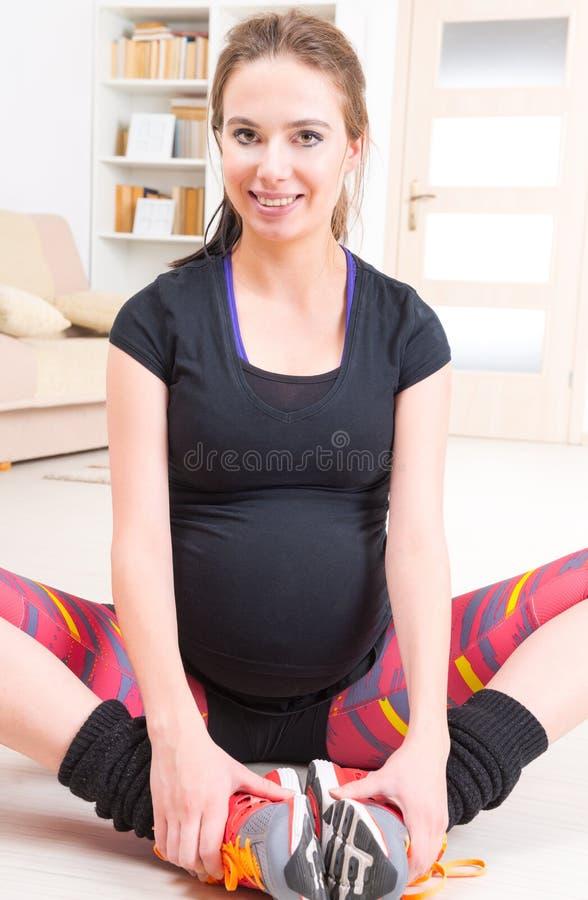 Mulher gravida que exercita em casa imagens de stock royalty free