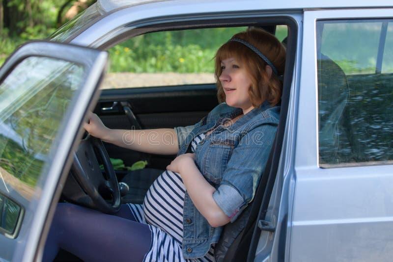 Mulher gravida que fala a sua barriga imagem de stock