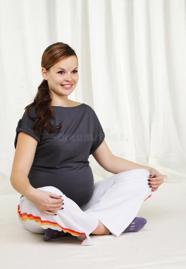 Mulher gravida que faz exercícios da ioga fotografia de stock