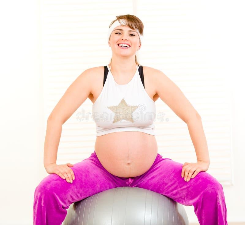 Mulher gravida que faz exercícios dos pilates na esfera fotos de stock royalty free