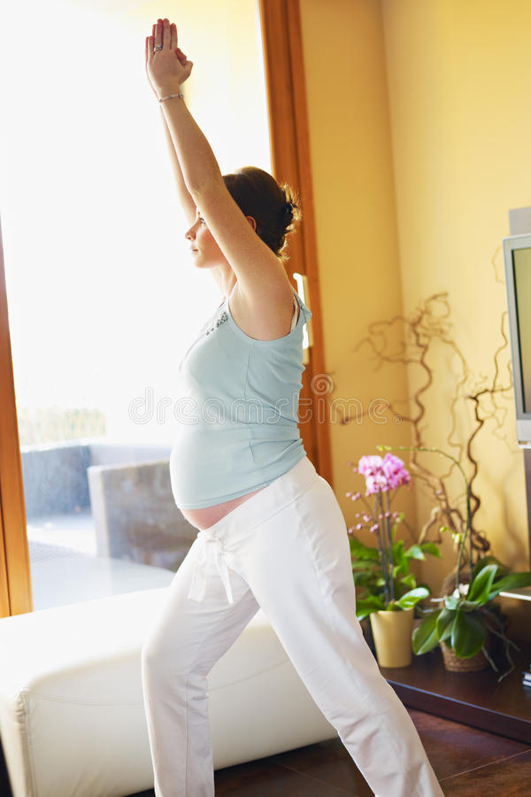 Mulher gravida que faz a ioga em casa fotos de stock