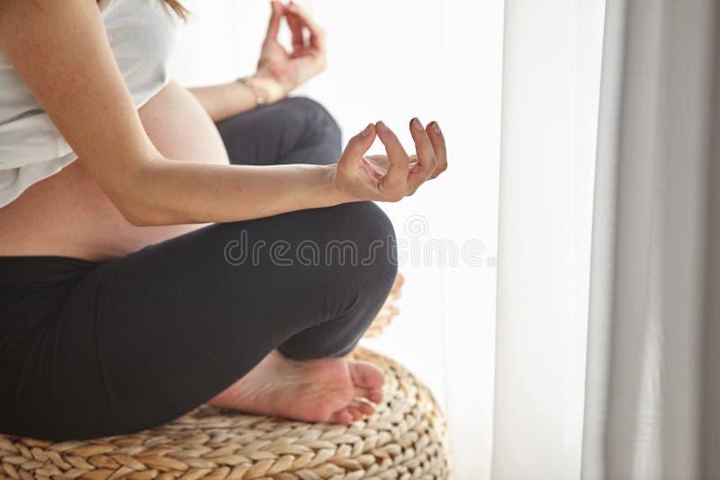 Mulher gravida que faz a ioga em casa imagens de stock royalty free