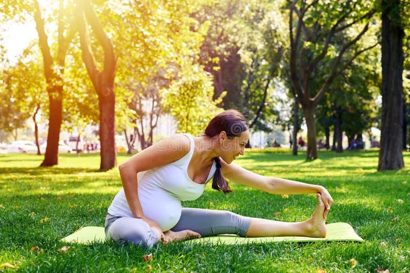 Mulher gravida que faz o exercício de relaxamento da ioga no parque imagens de stock royalty free
