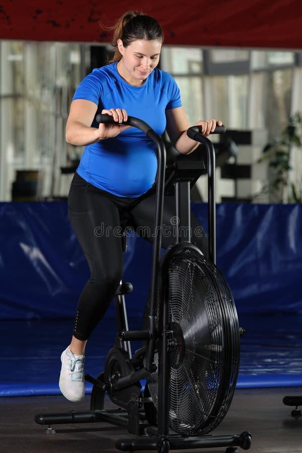 Mulher gravida que faz o exercício intenso na bicicleta do ar do gym fotografia de stock