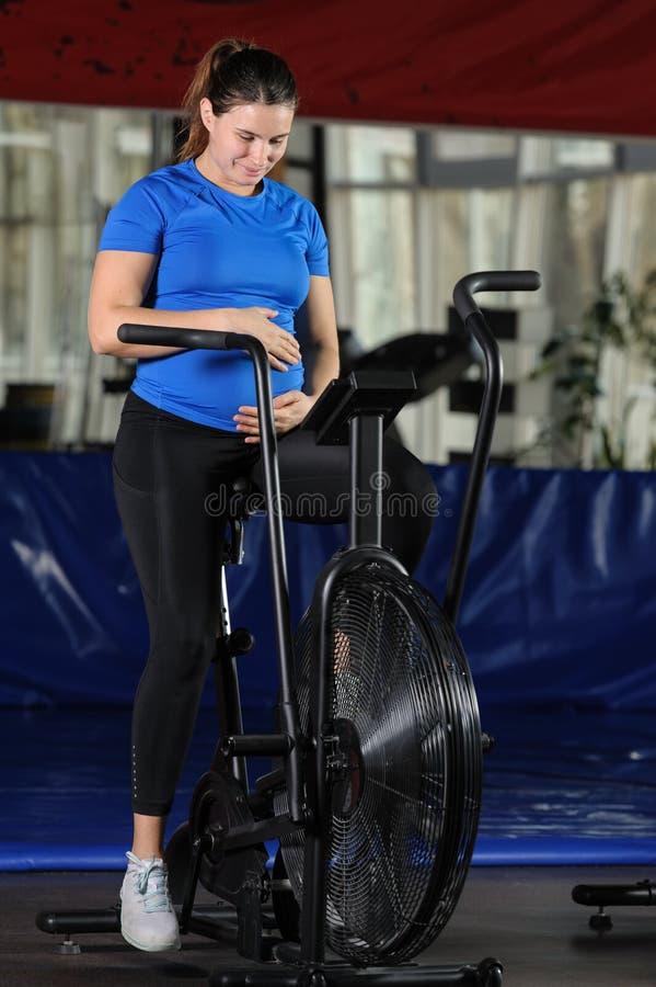Mulher gravida que faz o exercício intenso na bicicleta do ar do gym imagens de stock