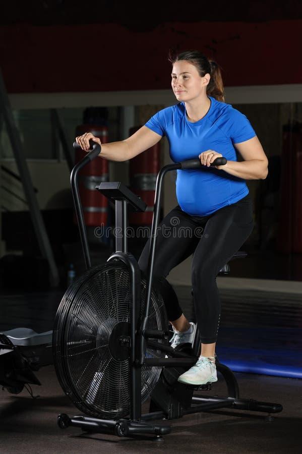 Mulher gravida que faz o exercício intenso na bicicleta do ar do gym imagem de stock royalty free
