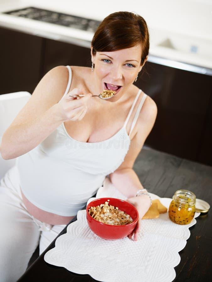Mulher gravida que faz o pequeno almoço em casa imagem de stock
