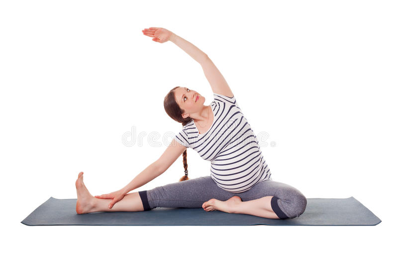 Mulher gravida que faz o sirsasana do janu de Parivrtta do asana da ioga foto de stock royalty free