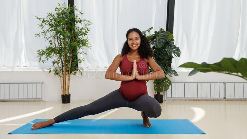 Mulher gravida que faz a pose da ioga foto de stock royalty free