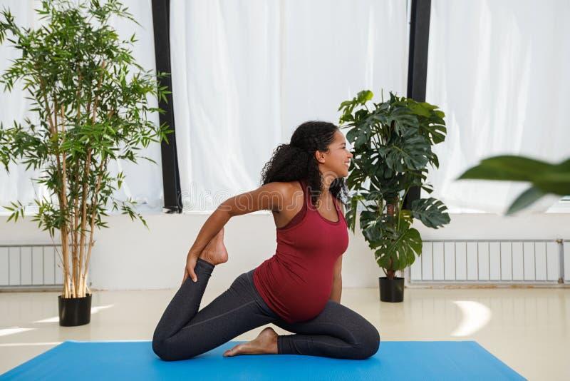 Mulher gravida que faz pose onelegged do pombo do rei fotos de stock royalty free