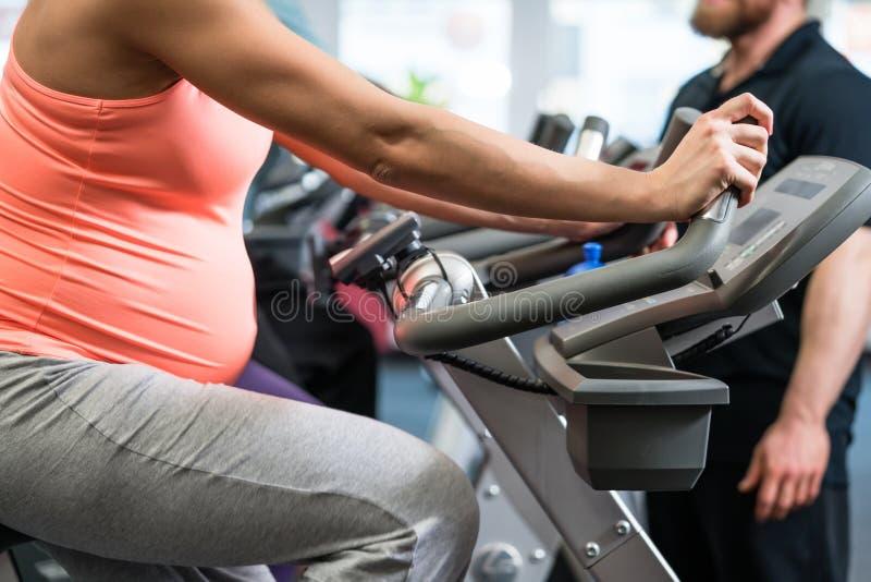 Mulher gravida que gira na bicicleta da aptidão no gym fotos de stock