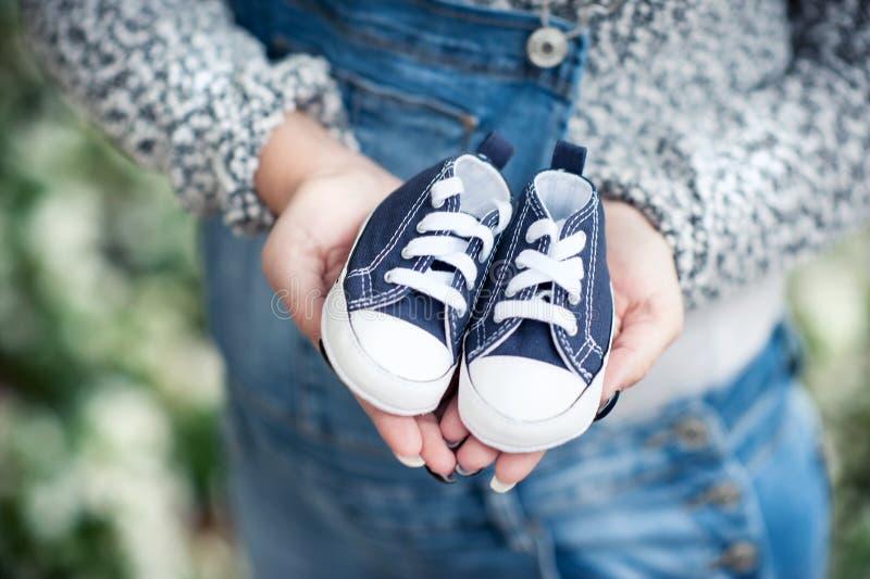 Mulher gravida que guarda sapatas pequenas para seu bebê imagens de stock