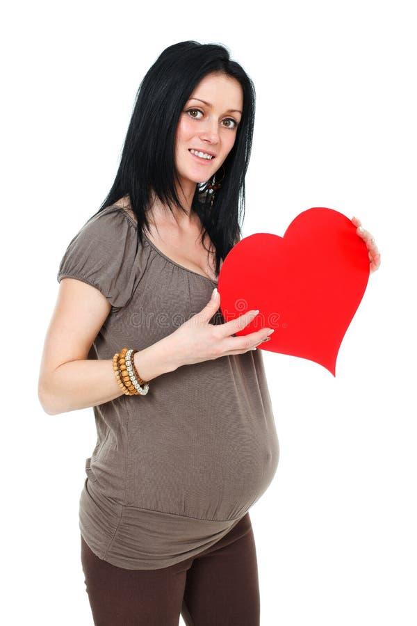 Mulher gravida que guardara o coração foto de stock