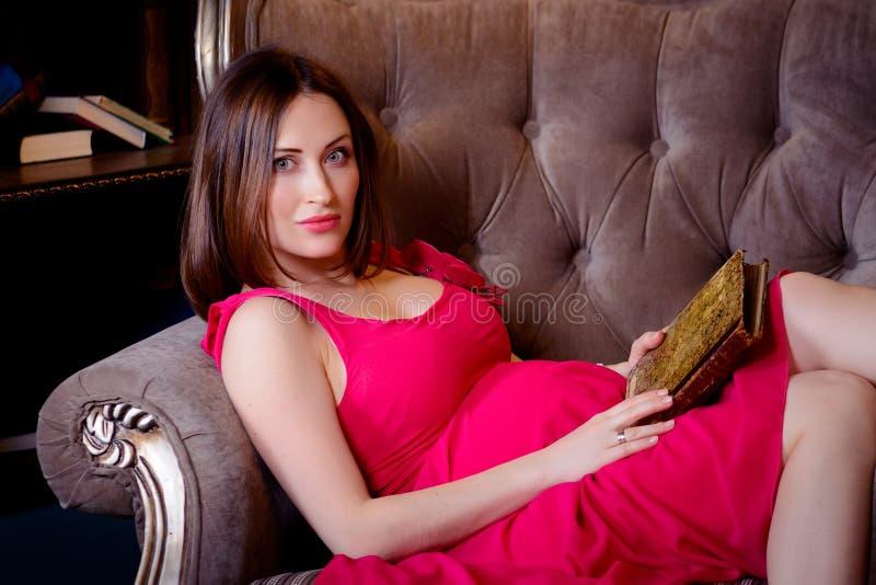 Mulher gravida que lê um livro que encontra-se no sofá imagem de stock