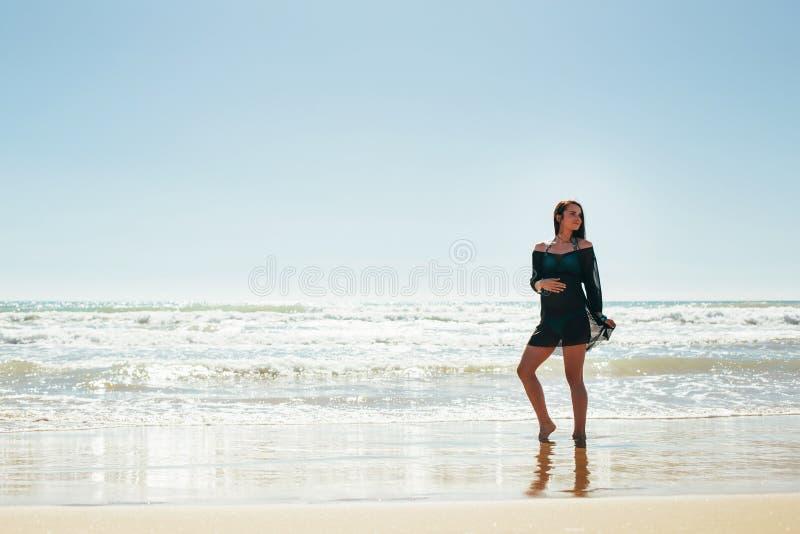 Mulher gravida que levanta na praia imagens de stock