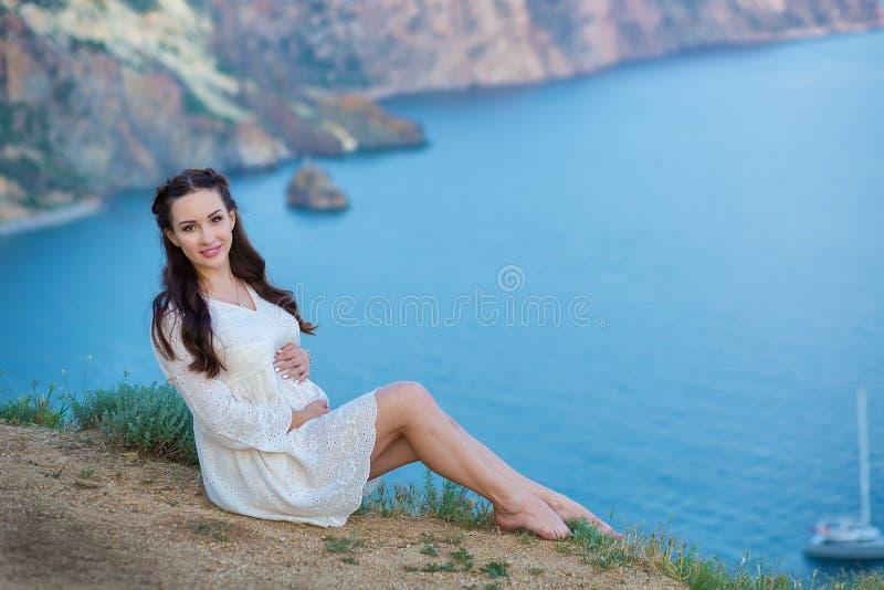 Mulher gravida que levanta o assento na montanha do penhasco que veste o vestido pairoso do whit com o mar azul no fundo fotografia de stock