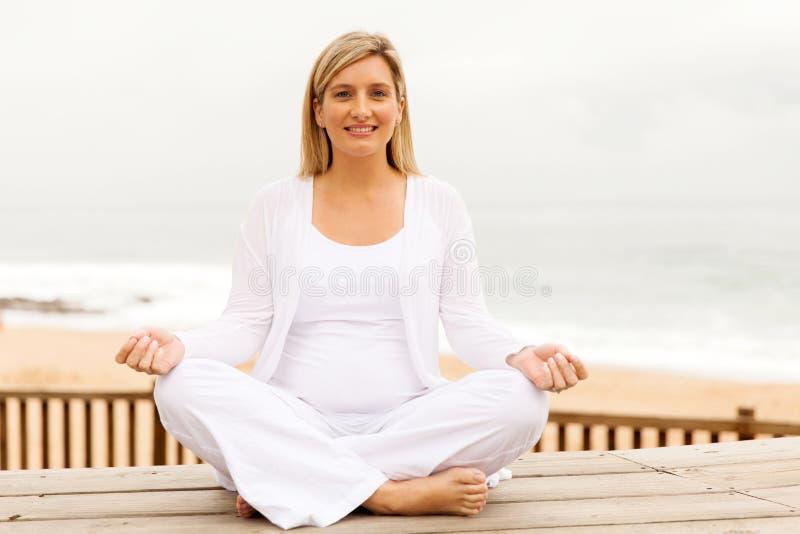 Mulher gravida que Meditating foto de stock