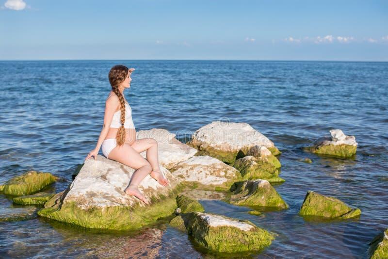 Mulher gravida que meditating em um pose da ioga no mar imagem de stock royalty free