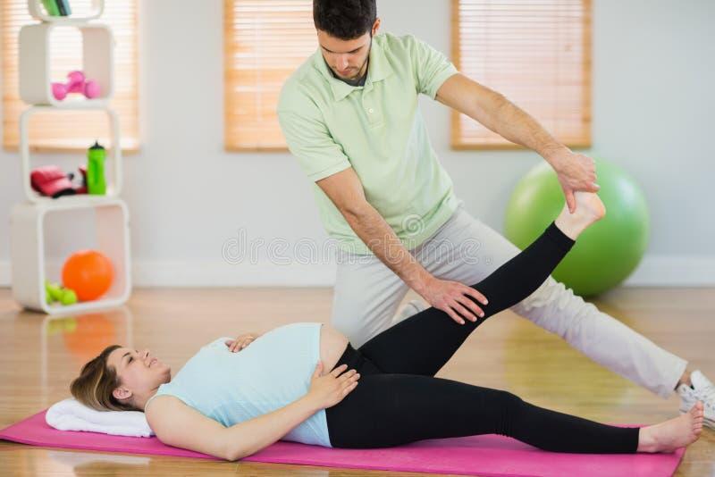 Mulher gravida que obtém a massagem de relaxamento imagem de stock