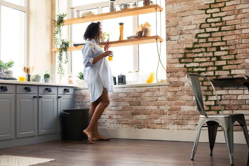 Mulher gravida que olha fora de sua janela da cozinha fotos de stock royalty free