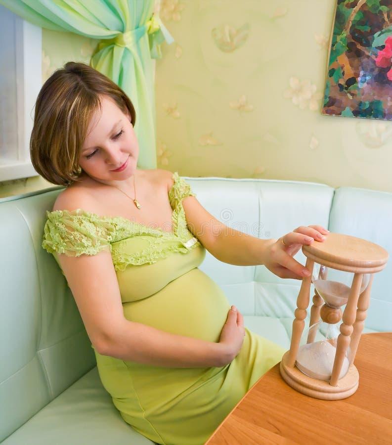 Mulher gravida que olha no hourglass imagem de stock royalty free