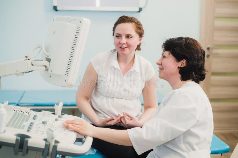 A mulher gravida que olha tiros do ultrassom de seu bebê crescente mostrou por seu doutor durante o exame médico imagem de stock