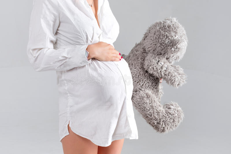 Mulher gravida que prende o brinquedo macio Urso de peluche levando da jovem mulher bonita imagens de stock
