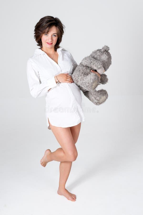 Mulher gravida que prende o brinquedo macio Urso de peluche levando da jovem mulher bonita imagem de stock royalty free