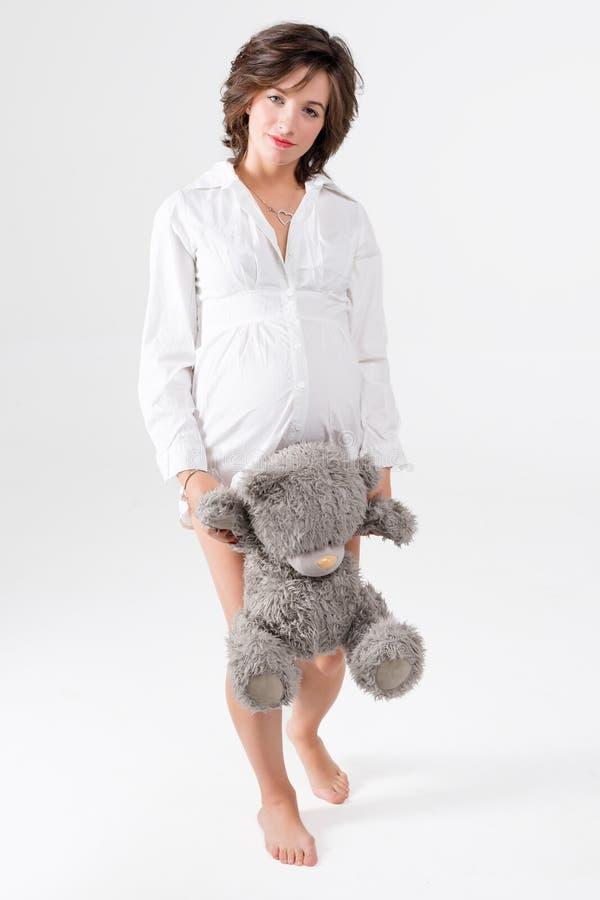 Mulher gravida que prende o brinquedo macio Urso de peluche levando da jovem mulher bonita fotos de stock