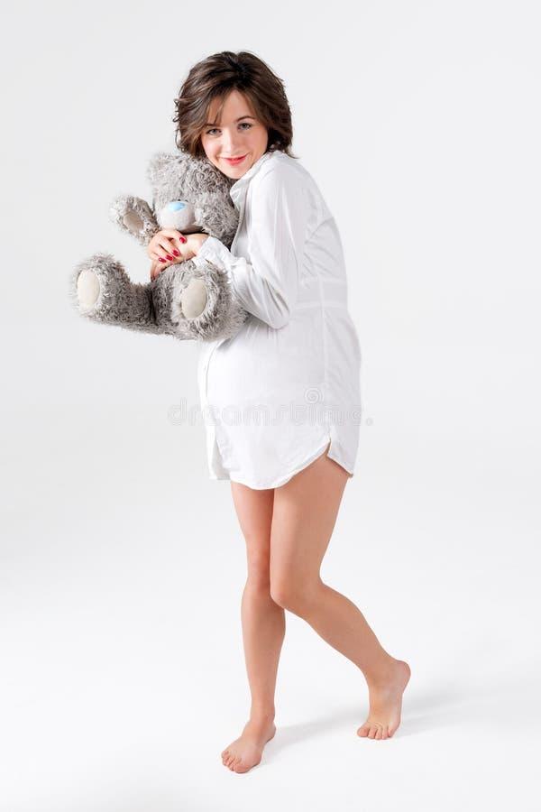 Mulher gravida que prende o brinquedo macio Urso de peluche levando da jovem mulher bonita foto de stock royalty free